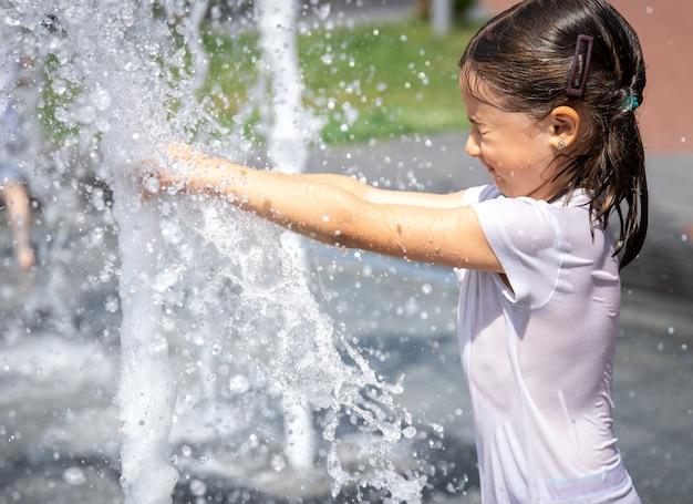街の噴水のしぶきの中の幸せな少女は楽しんで、暑さから逃げます。