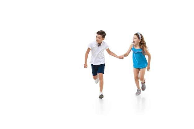 흰색 배경에서 실행하는 행복한 어린 소녀와 소년