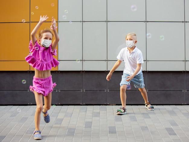 Счастливая маленькая девочка и мальчик в защитной маске, прыгающей и бегущей по улице города. copyspace. детство, концепция пандемии. здравоохранение, пандемия коронавируса.
