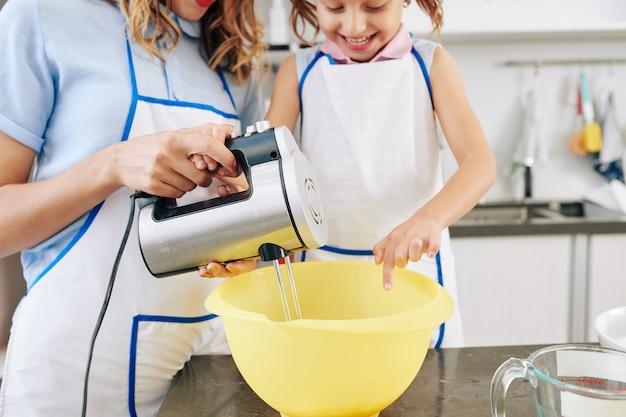 Счастливая маленькая девочка и ее мама замешивают тесто для блинов в большой пластиковой миске электронным миксером