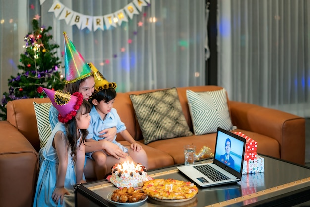 화상 통화에 아버지와 함께 집에서 그녀의 어머니와 함께 생일을 축하하는 행복 한 어린 소녀와 아들