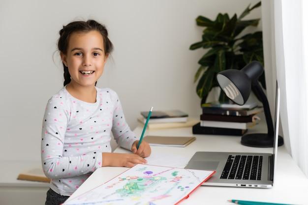 Счастливая маленькая девочка дома, работающая с ноутбуком