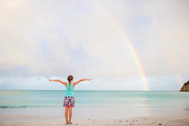 Happy little girl backgound the beautiful rainbow over the sea