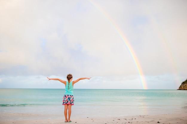 幸せな少女、海の上の美しい虹を背景に