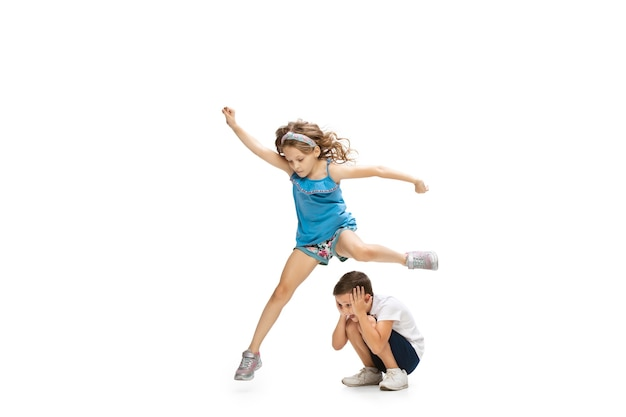 Happy little girl and boy running on white wall