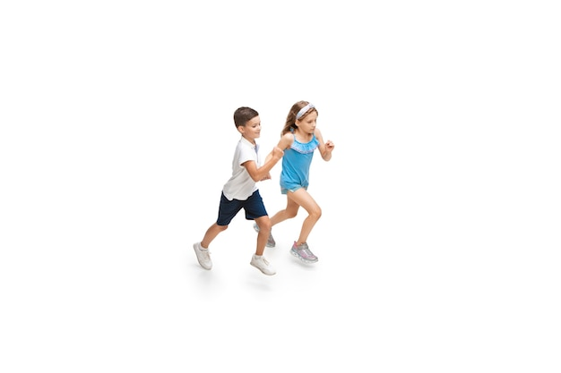 Happy little girl and boy running on white