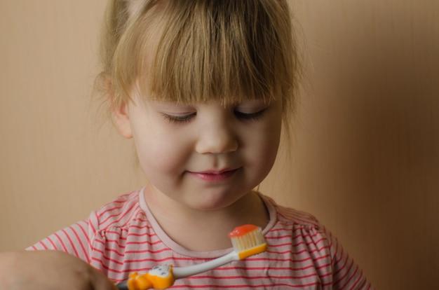 Happy little girl brushing her teeth. copy space