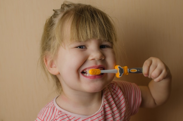 Happy little girl brushing her teeth. copy space