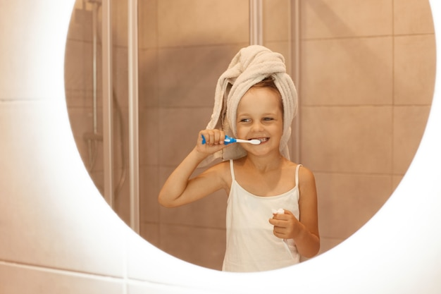 Счастливая маленькая девочка чистит зубы в ванной комнате, глядя на свое отражение в зеркале, в белой футболке и завернув волосы в полотенце, утренние гигиенические процедуры.
