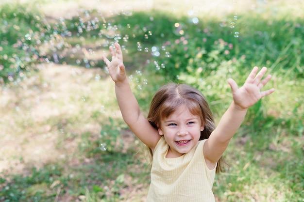 비누 방울을 잡는 행복한 어린 소녀