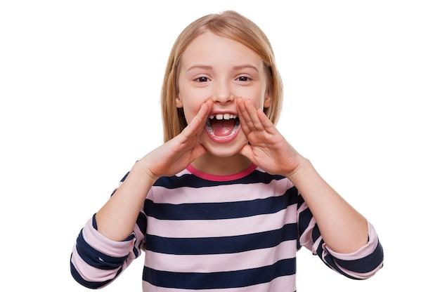 Счастливая маленькая девочка. веселая маленькая девочка кричит и держится за руки возле рта, стоя изолированной на белом