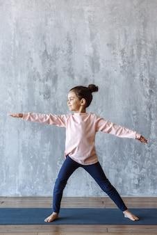 Счастливый маленькая девочка делает упражнения йоги, стоя в позе войны