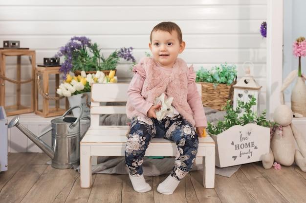 幸せな小さな女の子の子供1歳の子供のための自由な時間の活動の概念を離れて目をそらしている裏庭の笑顔でベンチに座っています