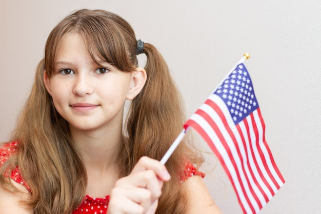 Happy little girl child in red dress holding usa flag