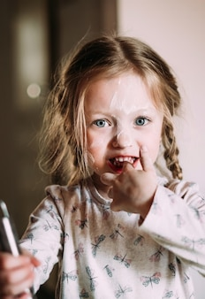 Счастливый ребенок маленькой девочки стоит в портрете конца-вверх кухни с мукой на стороне.