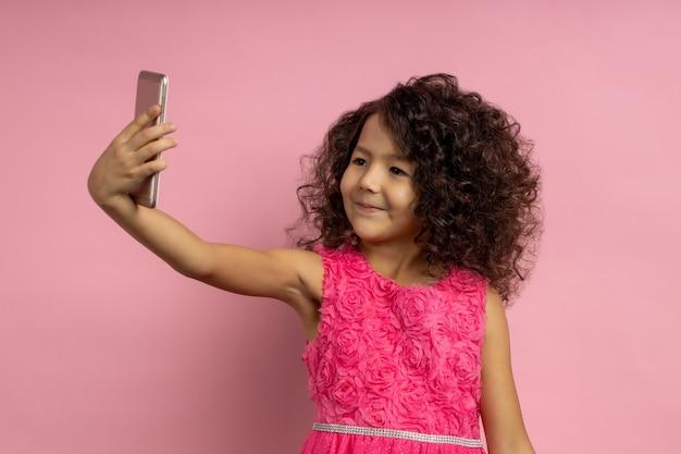 巻き毛の髪型、茶色の肌、パーティードレス、スマートフォンで自分撮りを撮る、ビデオ通話、孤立した幸せな少女の子供。テクノロジー、ライフスタイル、子供、ガジェットのコンセプト
