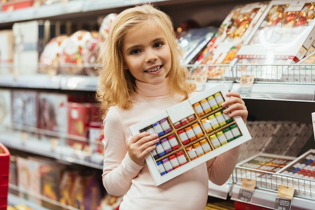 Happy little girl choosing candy