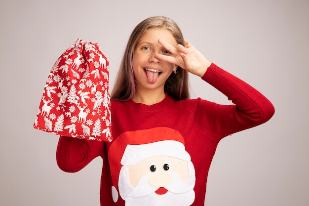 Happy little girl in christmas sweater holding santa red bag with gifts looking at camera smiling cheerfully showing v-sign near eyes sticking out tongue standing over white background
