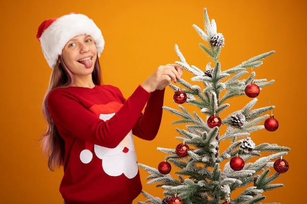 Happy little girl in christmas sweater and santa hat hanging balls on a christmas tree sticking out tongue over orange background
