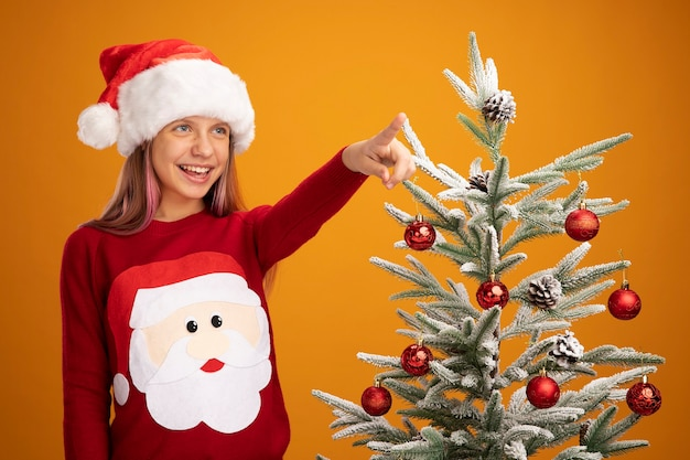 Happy little girl in christmas sweater and santa hat looking aside pointing with index finger at something smiling cheerfully standing next to a christmas tree over orange background