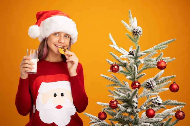 Happy little girl in christmas sweater and santa hat with glass of milk biting cookie smiling standing next to a christmas tree over orange background