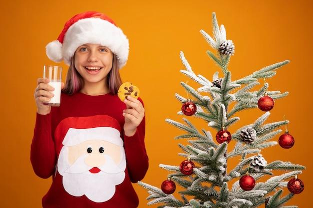Felice bambina in maglione di natale e cappello da babbo natale con un bicchiere di latte e biscotto guardando la telecamera sorridendo allegramente in piedi accanto a un albero di natale su sfondo arancione