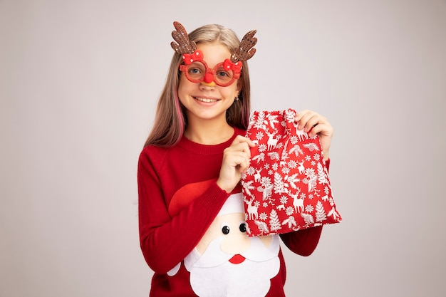 Happy little girl in christmas sweater wearing funny party glasses holding santa red bag with gifts looking at camera smiling cheerfully standing over white background