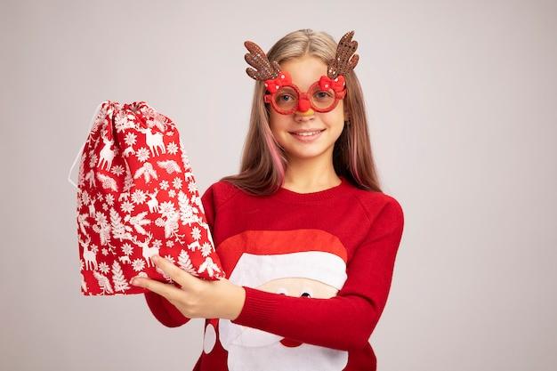 Bambina felice con un maglione natalizio che indossa occhiali da festa divertenti con in mano una borsa rossa di babbo natale con regali guardando la telecamera sorridendo allegramente in piedi su sfondo bianco