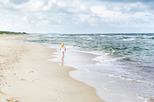 Happy little girl in clothes on the baltic sea beach on the curonian spit in lithuania.