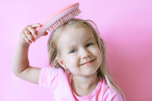 Счастливая маленькая девочка, расчесывая волосы. концепция красоты и детства. девушка на розовом изолированном фоне расчесывает волосы розовой расческой, ее светлые волосы