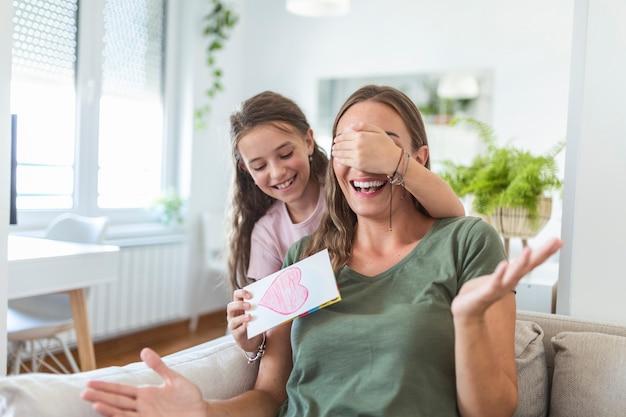 幸せな女の子は、笑顔の母親を祝福し、自宅での休日のお祝いの間に赤いハートでカードを与え、彼女の目を覆い、彼女を驚かせます