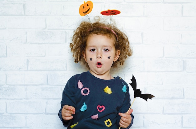 Happy little girl in costume with pumpkins, with painted spiders on her cheeks, holding bat and scaring boo. halloween kids.