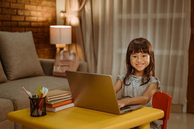 노트북을 사용 하여 숙제를 하 고 행복 한 어린 소녀
