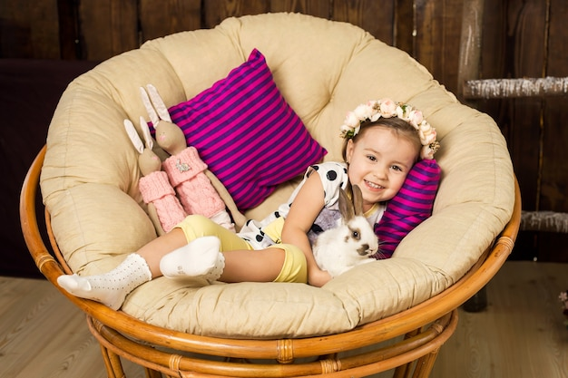 A happy little girl in a dress sits in a nest and holds a cute fluffy white easter bunny.