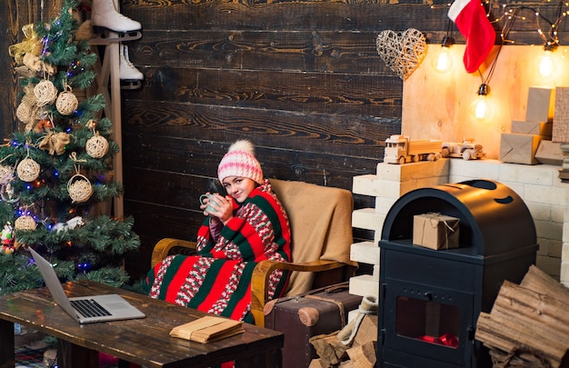 Happy little girl dressed in winter clothing think about santa near christmas tree happy smiling kid...