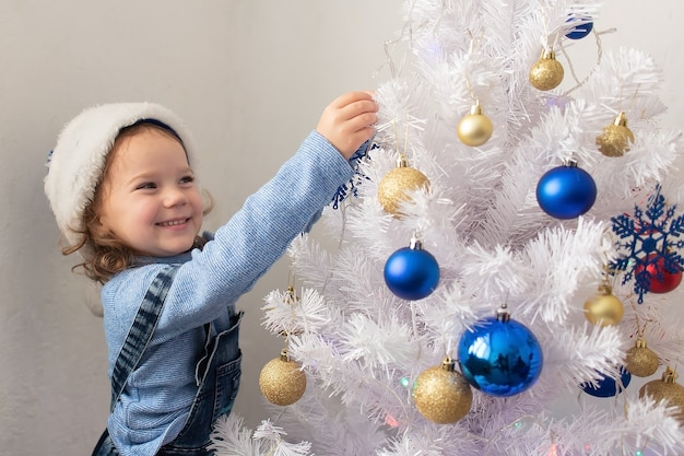 The happy little girl dresses up christmas tree