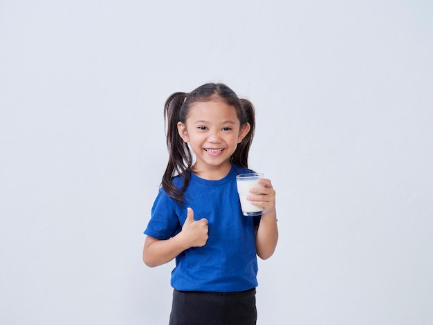 Happy little girl drinking milk and showing thumb up sign against light
