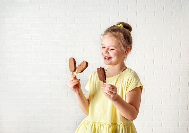 Happy little girl eating ice cream popsicles at summer time