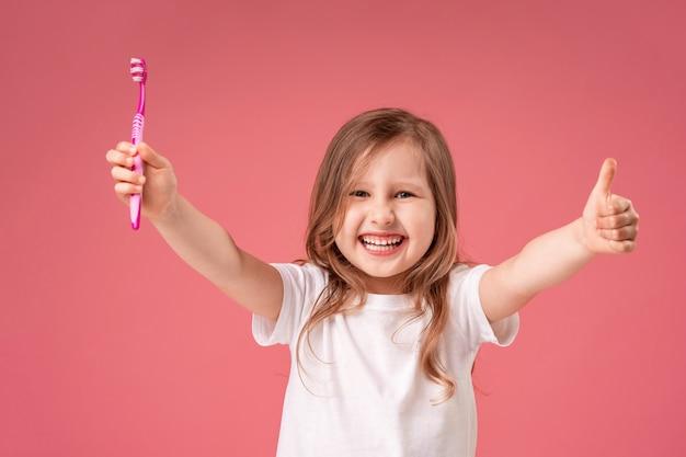 彼女の歯を磨くを楽しんで幸せな女の子