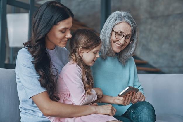 Счастливая маленькая девочка изучает смартфон, проводя время с мамой и бабушкой дома