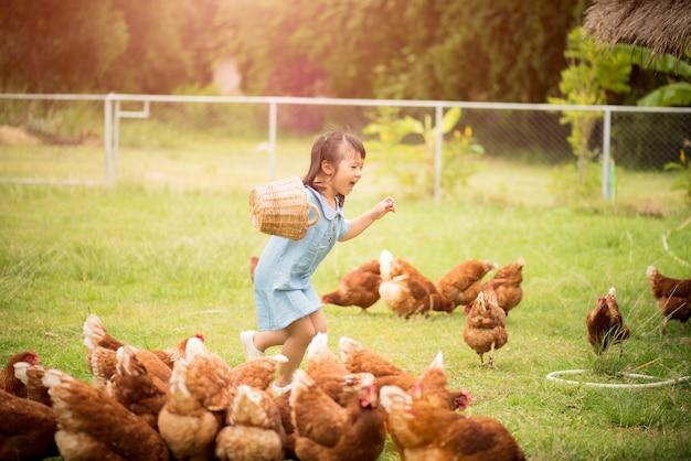 Счастливый маленькая девочка, кормление цыплят перед курица фермы.