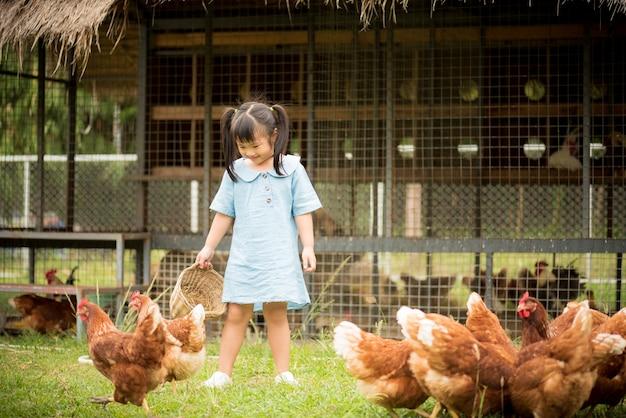 Счастливый маленькая девочка, кормящих цыплят перед курица фермы