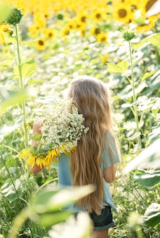 Happy little girl on the field of sunflowers in summer. Premium Photo
