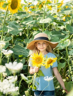 Happy little girl on the field of sunflowers in summer
