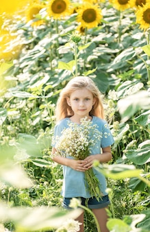 Happy little girl on the field of sunflowers in summer.