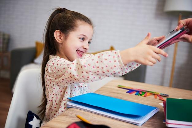숙제를 마치고 태블릿에 손을 뻗는 행복한 어린 소녀 무료 사진