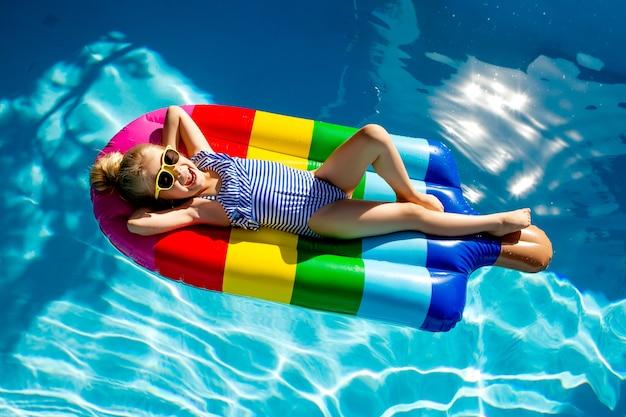 수영장에서 매트리스에 떠있는 행복 한 어린 소녀