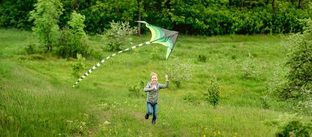 春の自然の中で明るい凧を屋外で飛んで幸せな少女