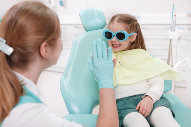 Happy little girl giving high five to her dentist after dental exam