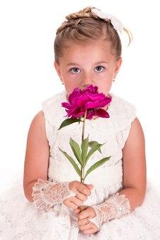 白い背景に牡丹の花を与える幸せな少女